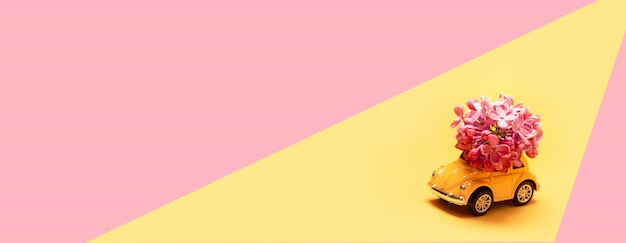 Yellow toy car delivers a bouquet of lilac on pink yellow Premium Photo