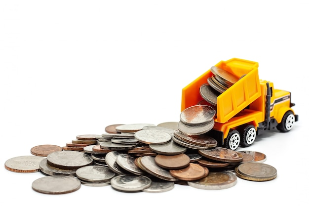 A yellow toy dump truck with pile of coins on white Premium Photo