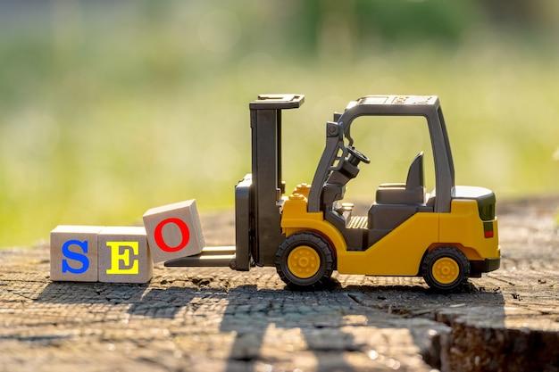 노란색 장난감 지게차는 나무 테이블에 단어 Seo (검색 엔진 최적화의 약어)를 완료하기 위해 문자 블록 O를 보유합니다. 프리미엄 사진