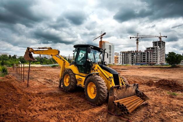 Желтый трактор на строительной площадке устанавливает столбы в поле Premium Фотографии