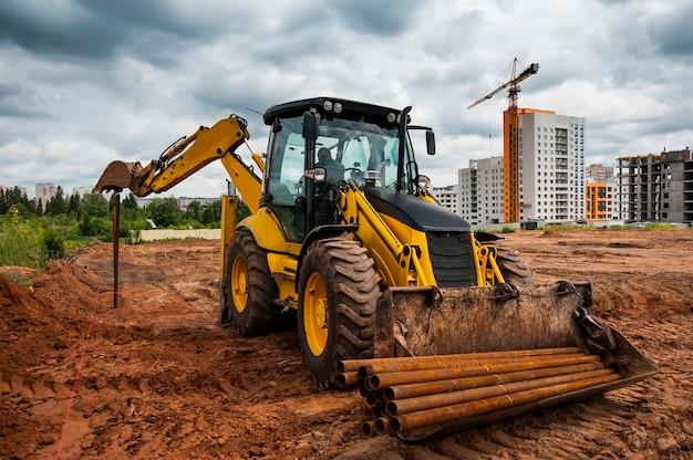 Желтый трактор устанавливает столбы в поле для нового строительства Premium Фотографии