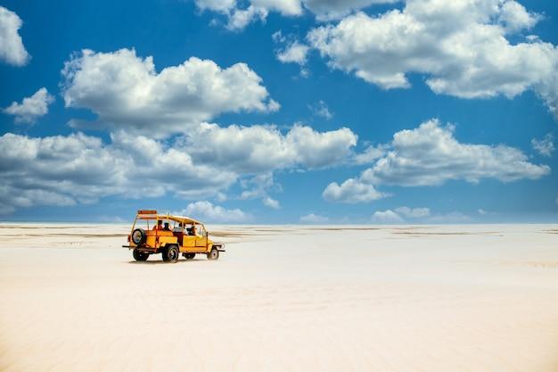 Желтый грузовик едет по песчаной земле под пасмурным голубым небом Бесплатные Фотографии