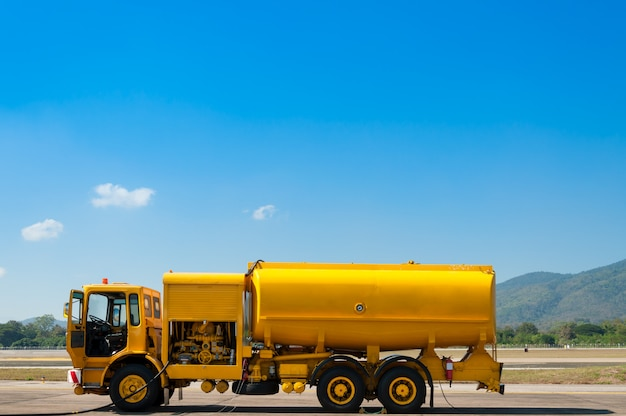 Yellow truck with fuel tank on runway Premium Photo