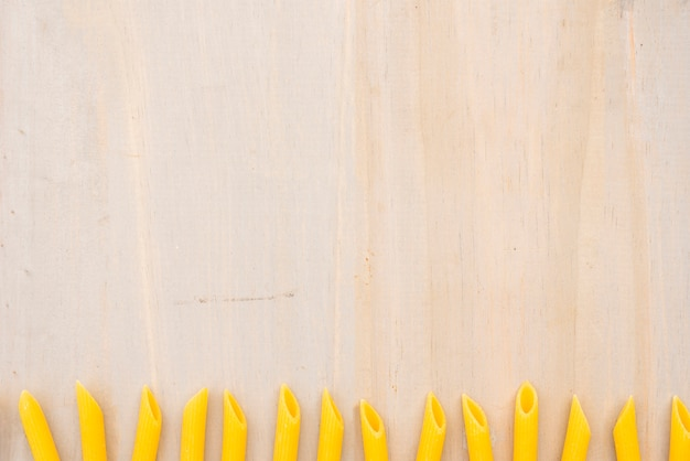 Yellow uncooked penne pasta arranged in row on wooden textured background Free Photo