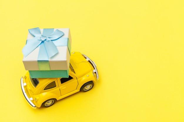 トレンディな黄色の背景に分離された屋根の上のギフトボックスを提供する黄色のビンテージレトロなおもちゃの車 Premium写真