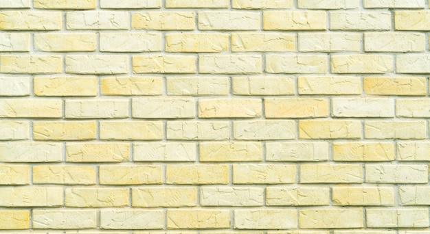 Yellow and white brick wall texture background with space for text. old bricks wallpaper. home interior decoration. Premium Photo