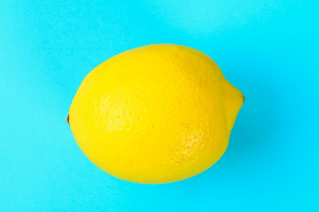 Yellow whole lemon on a pastel blue background. Premium Photo