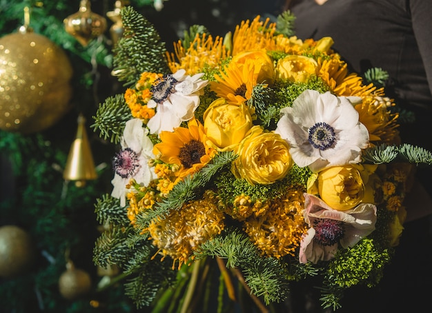Yellow winter bouquet with golden christmas ornaments Free Photo
