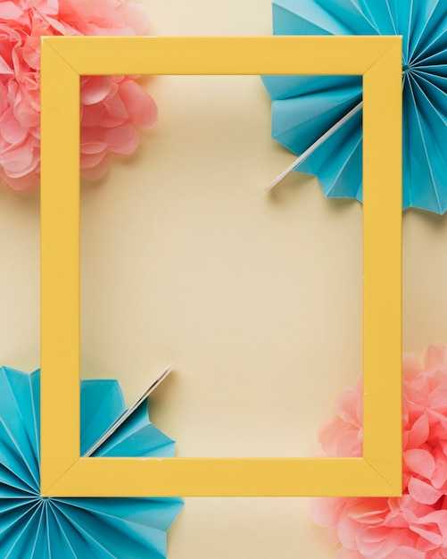 Yellow wooden border photo frame on paper flower over beige backdrop Free Photo