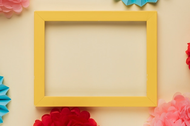 Yellow wooden border picture frame with decorated origami flowers Free Photo