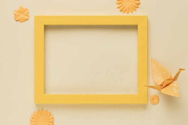 Yellow wooden frame with paper bird and flower cutout Free Photo