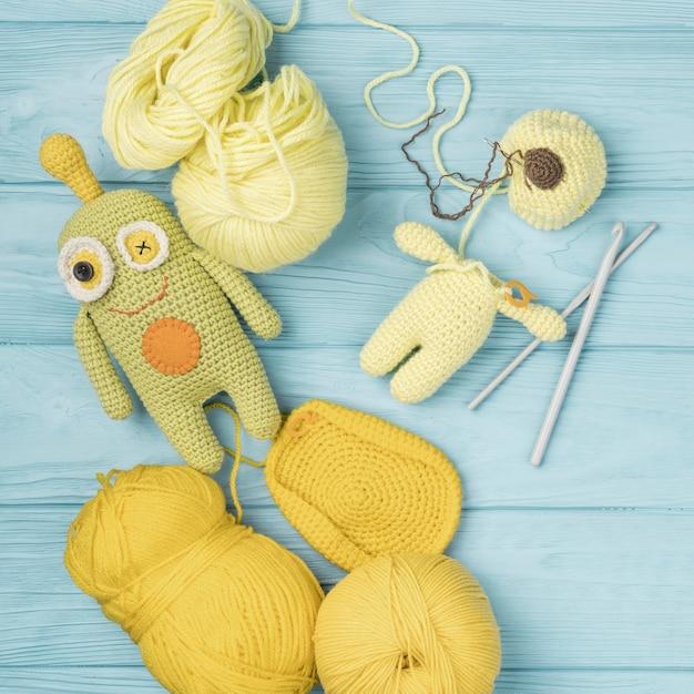 Yellow wool yarn with cute doll Free Photo