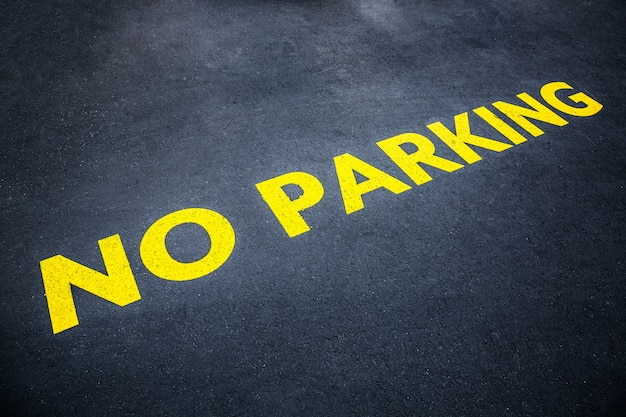Yellow words no parking painted on the road asphalt Premium Photo