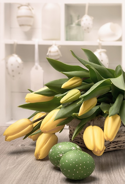 Yelow tulips, easter eggs and decorations in a shadowcase Premium Photo