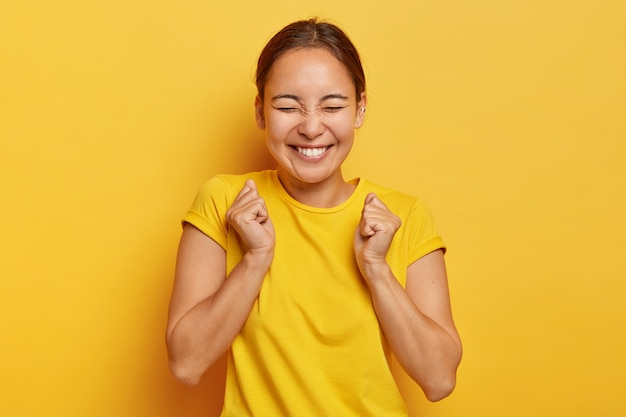 Yes, finally success! joyful korean girl clenches fists with triumph, closes eyes from happiness and joy, has toothy smile, wears casual outfit, isolated on yellow wall, triumphs victory Free Photo