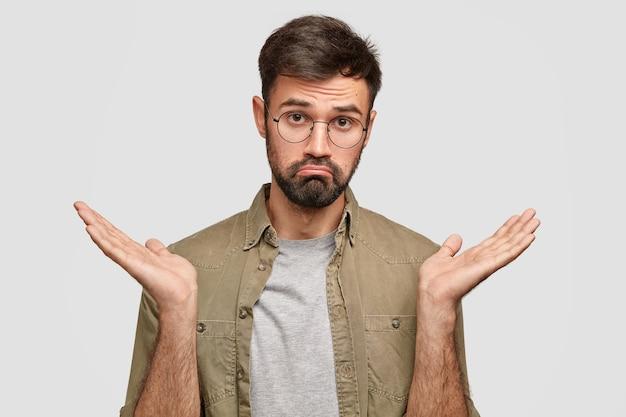 Да или нет? озадаченный нерешительный молодой человек пожимает плечами и поджимает губы, выглядит сомнительно и неуверенно, пытается принять решение. Бесплатные Фотографии