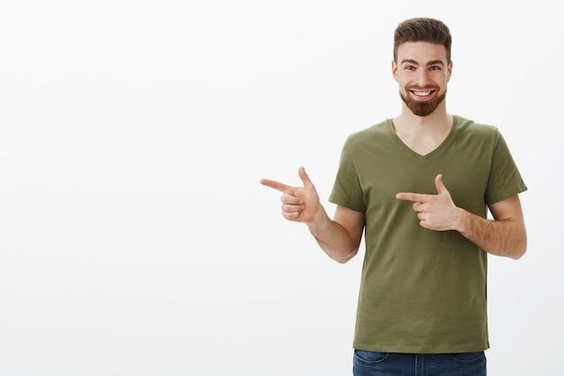 急いでチェックしてください。白い壁に素晴らしい製品を表示するために指のピストルで左を指すように喜んでオリーブtシャツ笑顔で熱狂的で興奮している魅力的なひげを生やした男の肖像 無料写真
