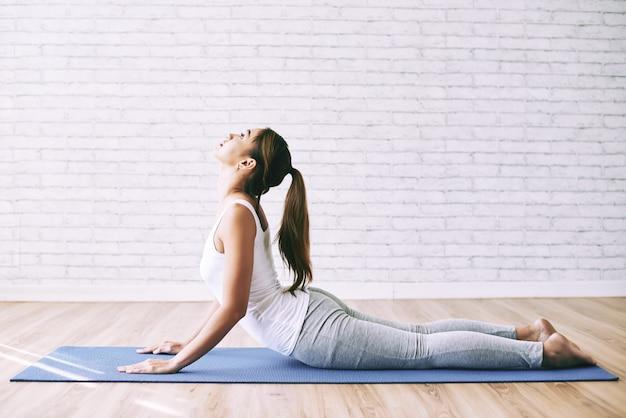 Yoga girl doing cobra asana as her morning exercise at home Free Photo