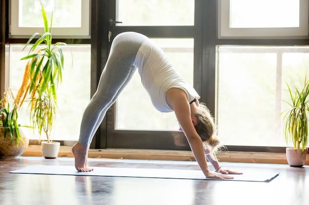 Yoga at home: downward facing dog pose Free Photo