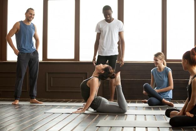 Esercitazione di yoga che esegue l'esercizio avanzato di raja bhudjangasana Foto Gratuite