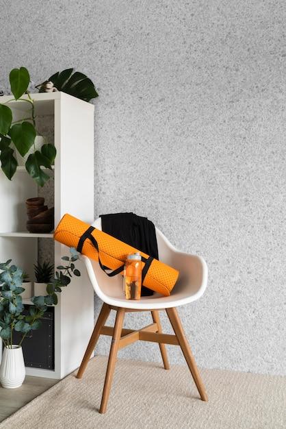 Коврик для йоги и бутылка с водой на стуле Бесплатные Фотографии