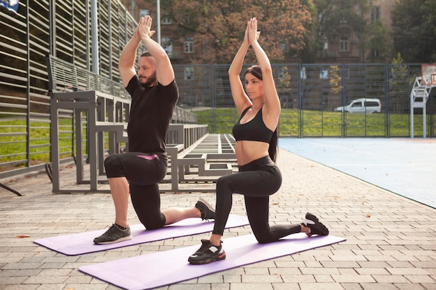 Yoga pose on mat with young sportives Free Photo