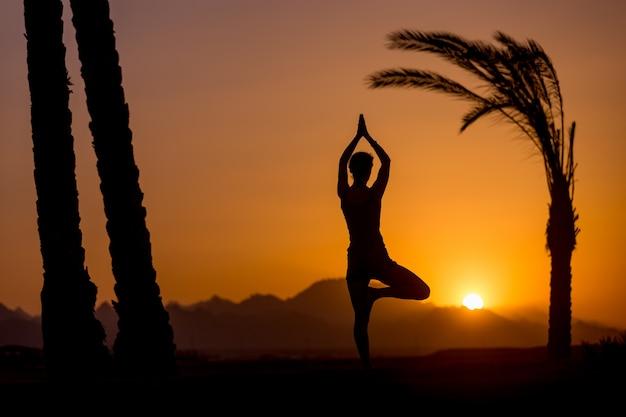 Yoga vrikshasana pose in tropical location Free Photo