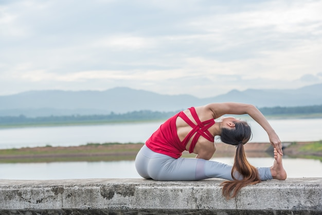 Yoga woman doing exercise at the lake. Premium Photo