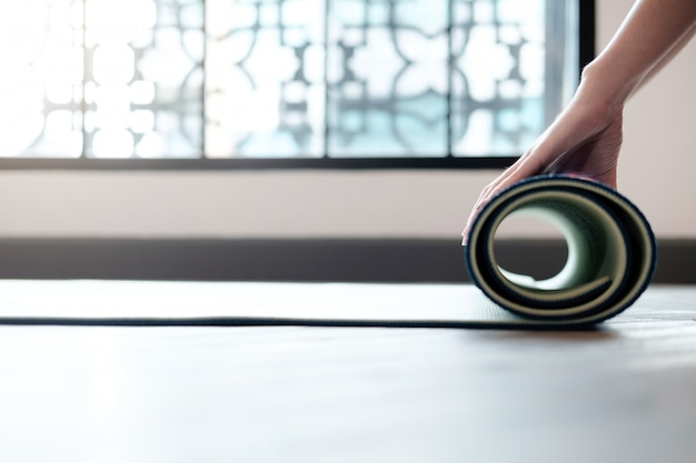 Yoga woman rolling her lilac mat after a yoga class Premium Photo