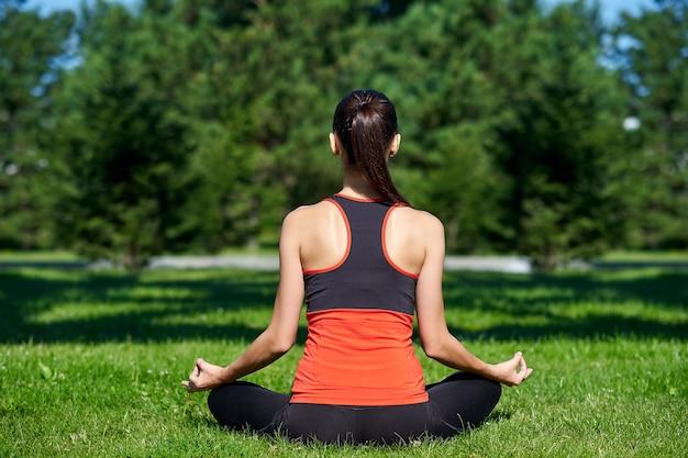 요가. 공원에서 자연 속에서 요가 명상을 연습하는 젊은 여자. 연꽃 자세. 건강 라이프 스타일 개념. 프리미엄 사진