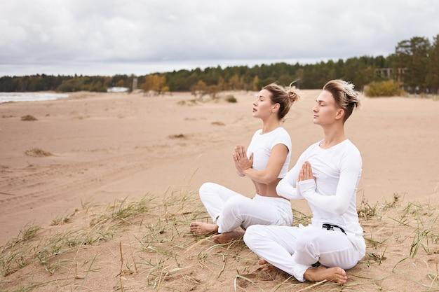 Йога, дзен, просветление, реактивация, медитация и концепция концентрации. молодые мужчины и женщины в белых одеждах медитируют с закрытыми глазами, делая жест намасте, сидя в позе лотоса Бесплатные Фотографии