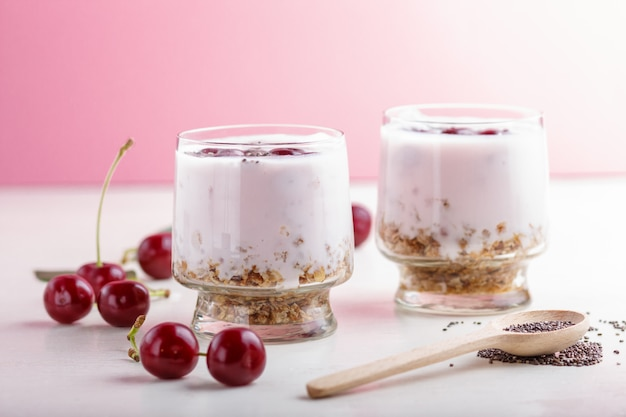 Yoghurt with cherries, chia seeds and granola in glass with wooden spoon. side  view Premium Photo