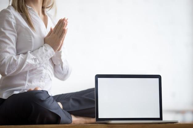 Yogi businesswoman with copy space laptop Free Photo