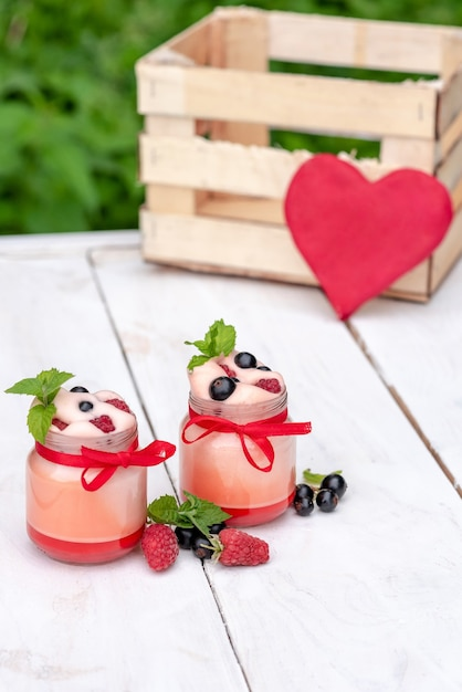 Йогурт на завтрак. со свежими ягодами на свежем воздухе. Premium Фотографии