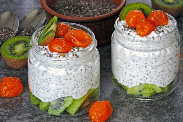 Yogurt with chia, kiwi and kumquat. white yogurt with fruit in jars. fitness breakfast. healthy food. keto diet. Premium Photo
