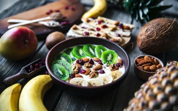 Йогурт с разными фруктами на деревянном столе. полноценное питание, диетическое, органическое. Premium Фотографии