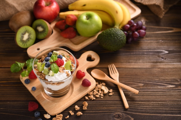 Yogurt with granola and fruits in glass on wooden table Premium Photo