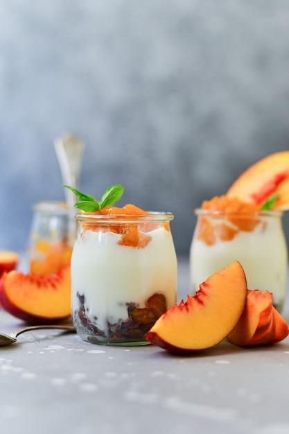 Yogurt with peach jam and fresh peaches in a round glass jar, dessert recipe. healthy breakfast Premium Photo