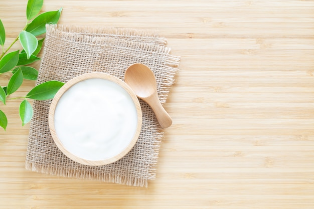Yogurt in wood bowl on white wooden table Premium Photo