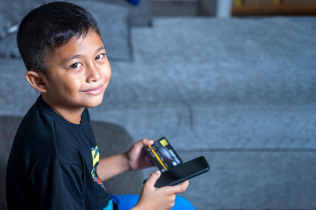 Yong asian children with yellow skin, holding black credit card, black laptop on white table. Premium Photo
