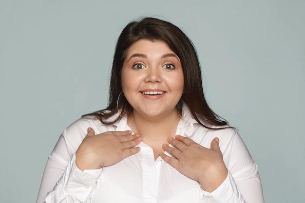 Ты имеешь ввиду меня. очарованная изумленная молодая женщина больших размеров в белой рубашке, указывая на себя, держась руками за грудь и широко улыбаясь, так как ее выбрали для положительной работы среди других кандидатов Бесплатные Фотографии