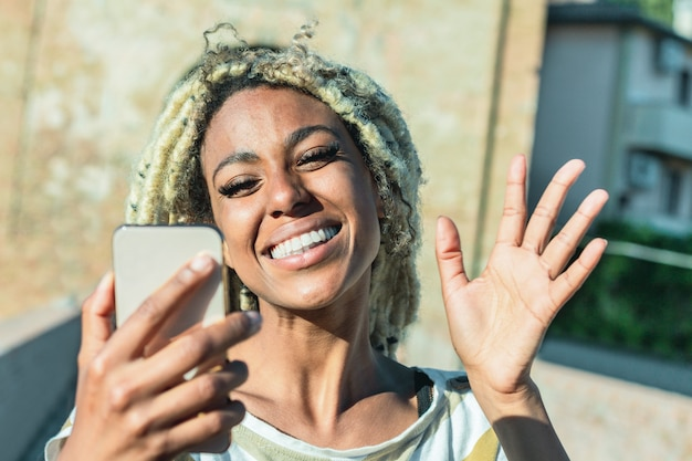Yound african woman with blond dreadlocks doing video call with smart mobile phone Premium Photo