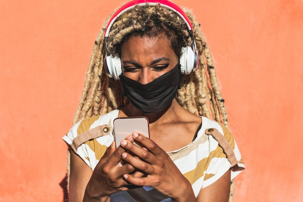 Yound african woman with blond dreadlocks using mobile phone while listening playlist music Premium Photo