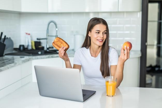 健康食品のコンセプトです。難しい選択。 youndスポーティな女性は、明るいキッチンに立っている間、健康食品とお菓子の間で選択しています。 無料写真