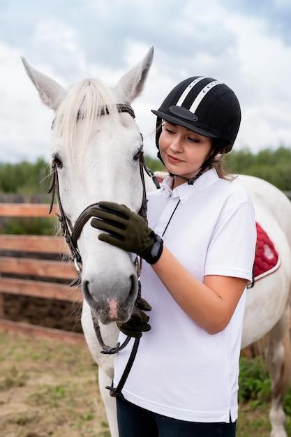 Молодая активная самка обнимает морду белой породистой скаковой лошади или кобылы во время холода в сельской местности Premium Фотографии
