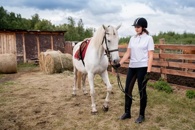 Молодая активная женщина в конном шлеме и спортивной одежде отдыхает со своей скаковой лошадью в сельской местности Premium Фотографии