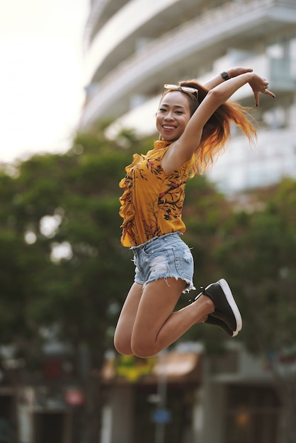 Young active woman performing a high jump in the street Free Photo