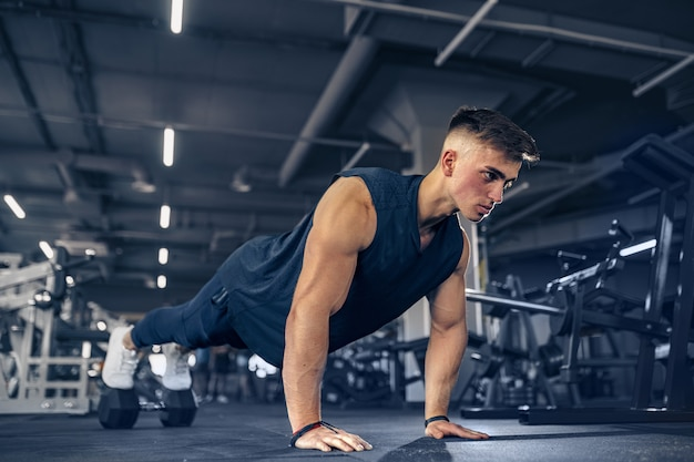 Young adult athlete doing push ups as part of bodybuilding training. Premium Photo