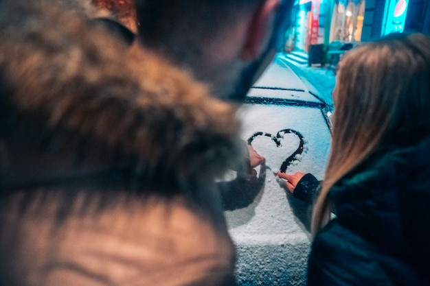 Young adult couple draws a heart on snow covered car Free Photo