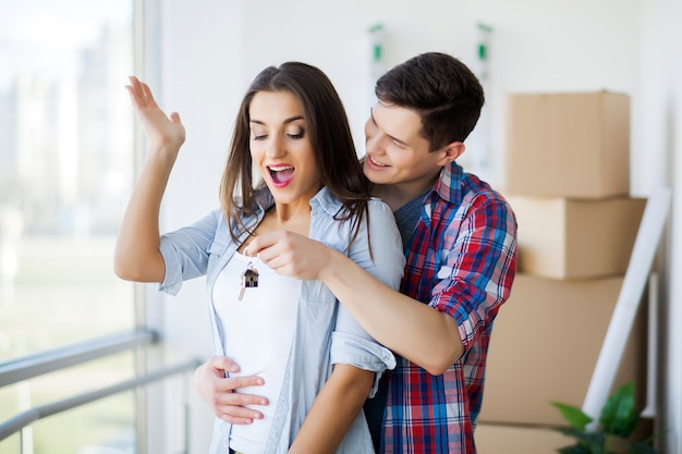 Young adult couple inside room with boxes holding new house keys banner. Premium Photo